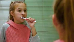 Borstar det gulliga härliga kvinnliga barnet för närbilden med ganska hår hennes tänder grundligt i spegelreflexion stock video