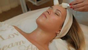 Borstar för kosmetolog som två gör massage på framsida för kvinna` s med ögon, stängde sig stock video