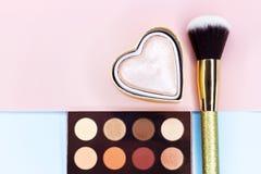 Borstar för smink, textur med skönhetsmedel på rosa färger och blåttbakgrund arkivfoto