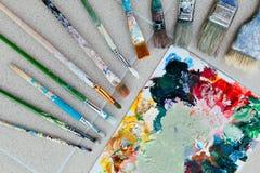 Borstar med paletten i den idérika bakgrunden Färgrikt element Royaltyfri Fotografi