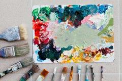 Borstar med paletten i den idérika bakgrunden Färgrikt element Royaltyfri Foto