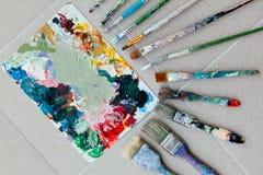 Borstar med paletten i den idérika bakgrunden Färgrikt element Arkivbild