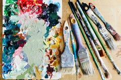 Borstar med paletten i den idérika bakgrunden Färgrikt element Arkivbilder