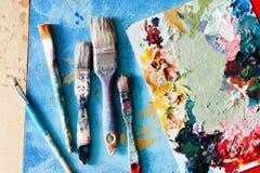 Borstar med paletten i den idérika bakgrunden Färgrikt element Arkivfoton