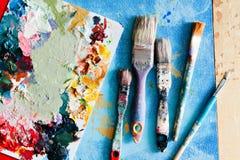Borstar med paletten i den idérika bakgrunden Färgrikt element Royaltyfri Bild
