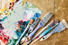 Borstar med paletten i den idérika bakgrunden Färgrikt element Royaltyfria Bilder