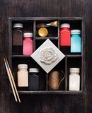 Borstar och målarfärger för att dra, i en träask, lägger framlänges royaltyfria foton