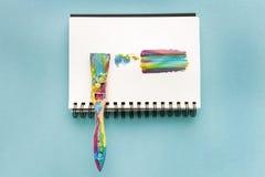 Borste och färgrikt penseldrag på papper på blått Arkivbild