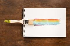 Borste och färgrikt penseldrag på papper på tabellen Arkivbild