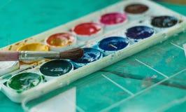 Borste- och vattenfärgmålarfärger på tabellen Arkivbild