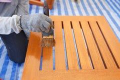 Borstel die in hand en op het houten meubilair schilderen royalty-vrije stock foto
