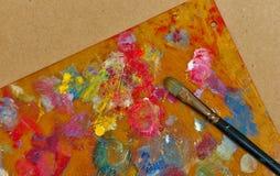 Borstel die op het kleurrijke palet van kleuren liggen Stock Fotografie