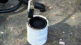 Borstel in een kruik van zwarte verf wordt doorweekt die stock videobeelden
