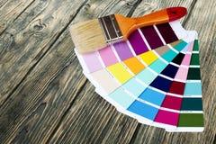Borstel en helder palet van kleuren op houten stock afbeelding