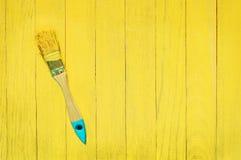 Borstel in gele verf op blauwe en gele houten achtergrond Stock Foto's
