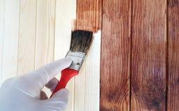 Borstel het in hand schilderen op de houten muur royalty-vrije stock afbeeldingen