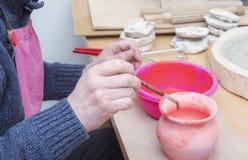 Borstel in man handen die op kleipot worden gebruikt om glans te zetten royalty-vrije stock afbeeldingen