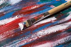Borstel op acrylverfachtergrond met blauwe en rode slagen stock foto's
