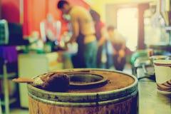 Borstel op houten emmer grondkoffie van koffiemachine met onscherp personeel stock afbeelding