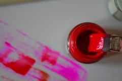 Borstel in rode verf wordt ondergedompeld die stock afbeeldingen