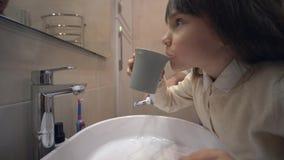 Borstelde de kinderen mondelinge hygiëne, leuk jong geitjemeisje tanden en spoelt mond met schoon leidingwater boven gootsteen bi stock videobeelden