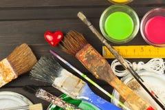 Borstels en verf op een houten lijst Schildershulpmiddelen Workshopschilder Behoeften het schilderen Verkoop die behoeften schild Royalty-vrije Stock Foto