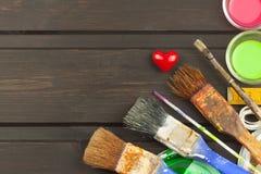 Borstels en verf op een houten lijst Schildershulpmiddelen Workshopschilder Behoeften het schilderen Verkoop die behoeften schild Royalty-vrije Stock Fotografie