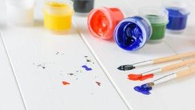Borstels met heldere kleuren op een witte houten lijst Creatieve Uitrusting Stock Afbeelding