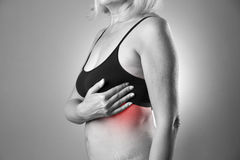 Borsttest, vrouw die haar borsten voor kanker, hartaanval onderzoeken stock fotografie