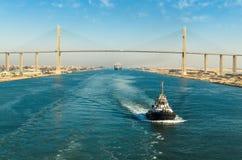 Bortgång för eskortfartyg för skepp` s till och med den Suez kanalen, i bakgrunden - bron för Suez kanal, Suez kanal, Egypten royaltyfri bild