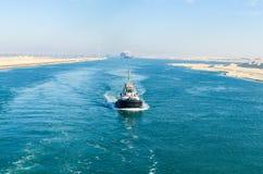 Bortgång för eskortfartyg för skepp` s till och med den Suez kanalen, i bakgrunden - bron för Suez kanal, Egypten royaltyfri bild