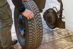 Borttagning av ett bilhjul och ett utbyte av vintern tröttar för sommar royaltyfri fotografi