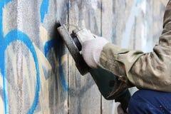 Borttagning av grafitti på en betongvägg av en underjordisk passage med hjälpen av en vinkelmolar royaltyfria bilder