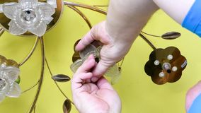Borttagning av ljuskronatangenten p? bakgrunden av ett gult elasticitetstak i dagsljus arkivfilmer