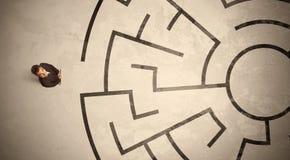 Borttappad affärsman som söker efter en väg i rund labyrint Arkivfoto
