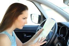 Borttappad chaufför som försöker att finna riktning i en handbok arkivbild