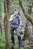 Borttappad fotvandrare i skog med den mobila satellit- navigeringapparaten Royaltyfria Bilder