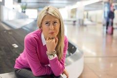 Borttappad frustrerad kvinna hennes bagage i flygplats Royaltyfri Fotografi