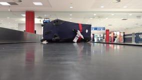 Borttappad resväska långsamt som är rörande på transportören i flygplatsen stock video