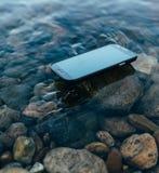 Borttappad smartphone på vattnet Royaltyfri Foto