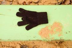 Borttappade woolen handskar på grön bänk Sandigt gren träbänken Sandlåda med smutsig sand i dagis Arkivbild