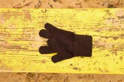 Borttappade woolen handskar på gul bänk Sandigt gren träbänken Sandlåda med smutsig sand i dagis Royaltyfri Bild