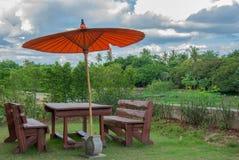 Borwn stolar och orange paraply i trädgård Arkivfoto