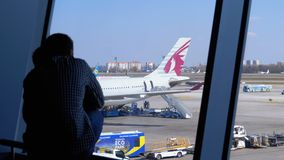 Silhouette of a little boy and father in front of the terminal window looking at the planes. Boryspil, Ukraine, April 3, 2019: Silhouette of a Little Boy and stock video footage