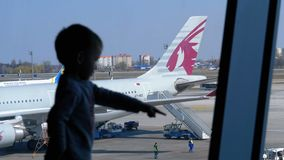 Silhouette of a little boy in front of the terminal window looking at the planes. Boryspil, Ukraine, April 3, 2019: Silhouette of a little boy in front of the stock video footage