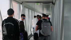 Boryspil/Ukraine-July,19 2019 - happy tourists going through plane gangway in Boryspil airport. Travelers going to airplane