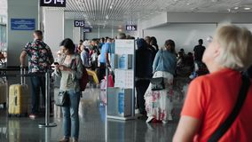 Boryspil/Ukraine-July,19 2019 - Male and female travelers with suitcases and tourist bags waiting for flight in Boryspil airport. Departure area in airport stock footage