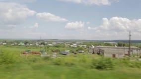 Bosättning i det ryska landskapet Filmande från fönstret av ett rörande drev field treen stock video