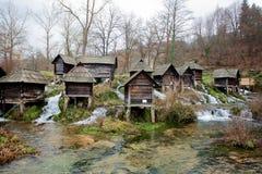 Bos met houten die watermolennen op een snelle en duidelijke rivier in de famouse toeristische plaats worden voortgebouwd Stock Afbeeldingen
