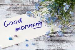 Bos van blauwe bloemenvergeet-mij-nietjes en goedemorgennota Stock Fotografie